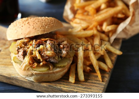 Tasty burger and french fries on plate, on wooden table background. Unhealthy food concept - stock photo