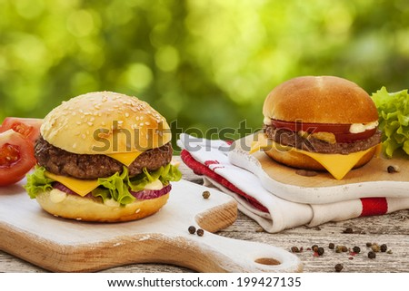Tasty burger with cheese, lettuce, onion and tomatoes served outdoor on a wooden table