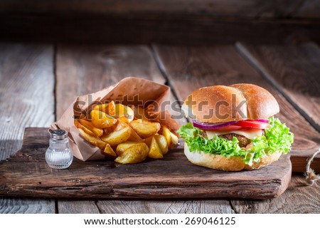 Tasty burger  with fries in old wooden board - stock photo
