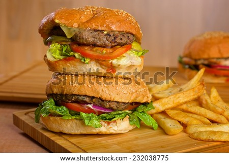 Tasty burger with melted cheese and a thick succulent ground beef patty garnished with lettuce, tomato, onion and rocket on a sesame bun standing on a picnic table in the garden