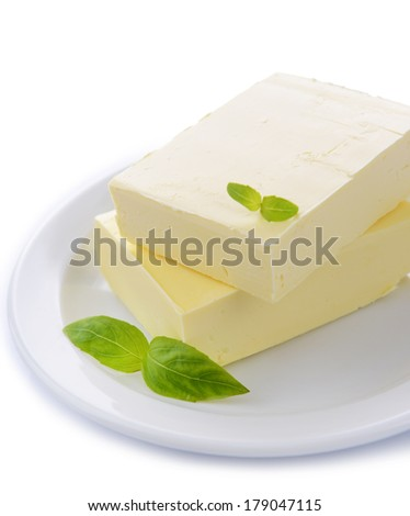 Tasty butter on plate isolated on white - stock photo