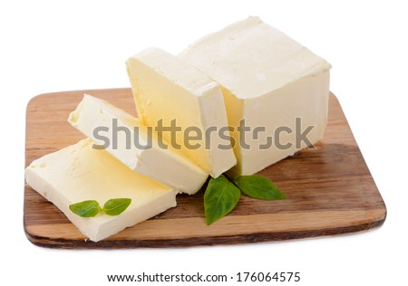 Tasty butter on wooden cutting board isolated on white - stock photo