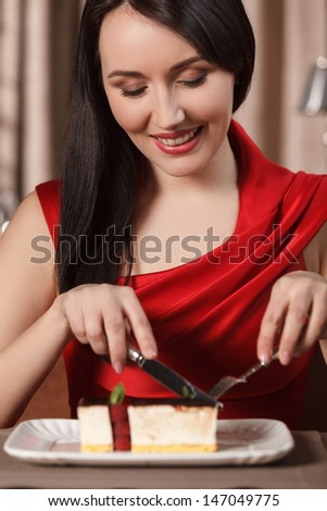 Tasty cake. Beautiful women in red dress eating cake at the restaurant - stock photo