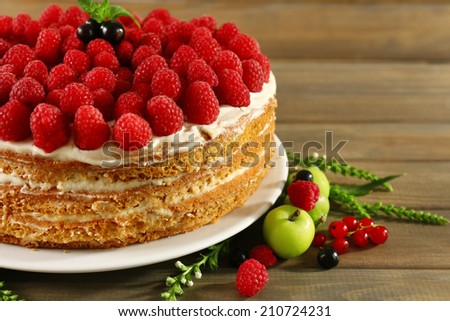 Tasty cake with fresh berries on wooden table - stock photo