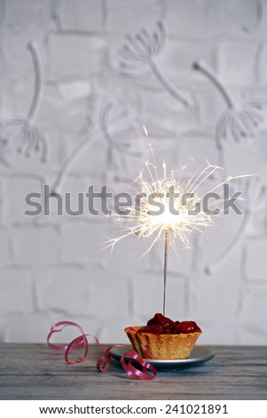 Tasty cake with sparkler on wooden table - stock photo