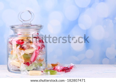 Tasty candies in jar on table on bright background - stock photo