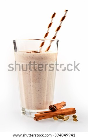Tasty chai latte, a spiced black Chinese tea blended with milk, cinnamon and cardamom with the dried spices alongside over white - stock photo