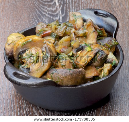 Tasty Champignon Mushrooms Stew with Onion and Greens in Black Cast-iron Stew Pot on Wooden background - stock photo