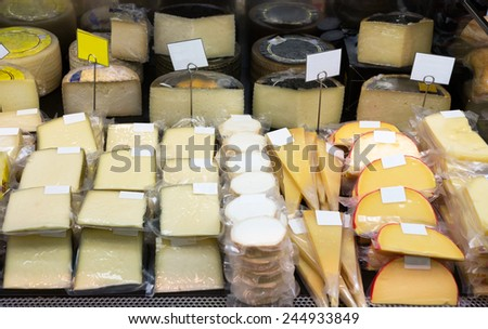 Tasty cheese in packs and in bulk on counter at store - stock photo