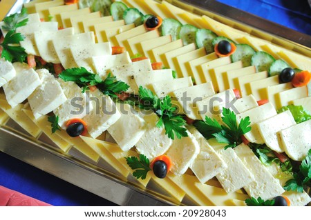 tasty cheese slices  and tasty food at buffet party food arrangement on table closeup - stock photo