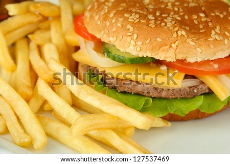 Tasty cheeseburger with fried potatoes, close up