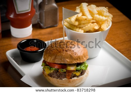 Tasty cheeseburger with fries. - stock photo
