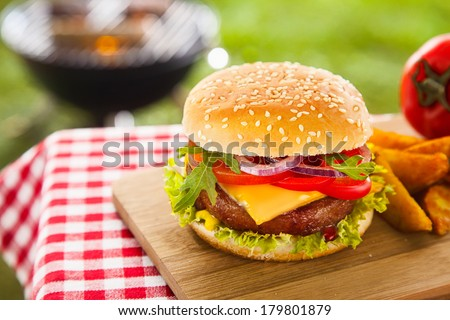 Tasty cheeseburger with melted cheddar cheese dripping over ground beef burger garnished with fresh salad ingredients and served on a wooden table on an outdoor picnic table - stock photo