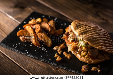 Tasty chicken doner kebab with fried potato on a wooden table - stock photo