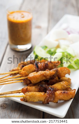 Tasty chicken satay on wooden dining table, one of famous Malaysian local dishes. - stock photo