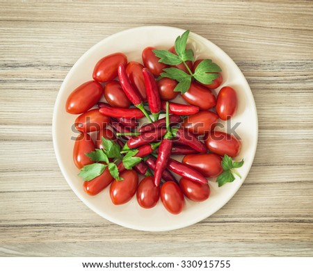 Tasty chili peppers and cherry tomatoes on the plate. Food theme. - stock photo