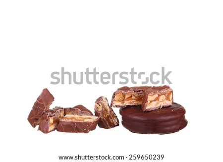Tasty chocolate bar split in two pieces. Delicious caramel cream and peanuts inside.White background. - stock photo