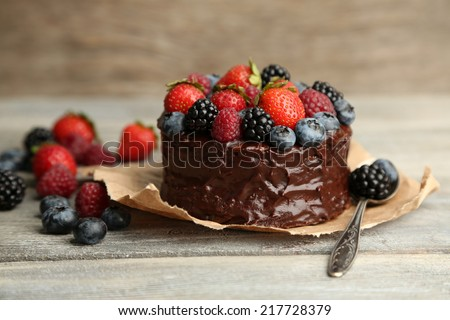 Tasty chocolate cake with different berries on wooden table - stock photo
