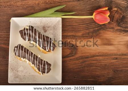 Tasty chocolate eclair and cream - stock photo