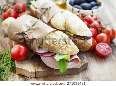 Tasty Ciabatta Sandwiches with Italian Mortadella, Green Lettuce and Radish Slices - stock photo