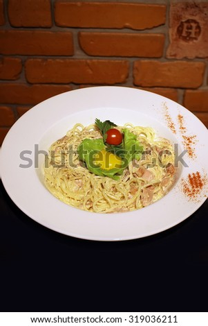 Tasty classical pasta carbonara with bacon egg yolk parmesan cheese decorated with leaf lettuce and red cherry tomato on white round plate closeup, vertical picture - stock photo