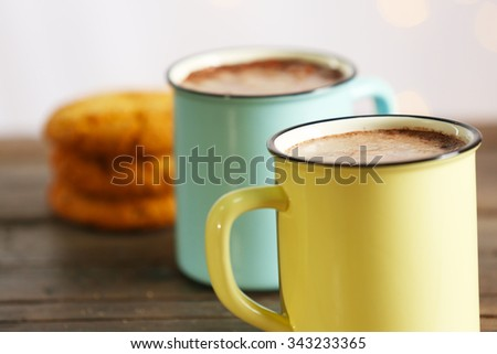 Tasty cocoa in metal old-fashioned mugs on the table - stock photo