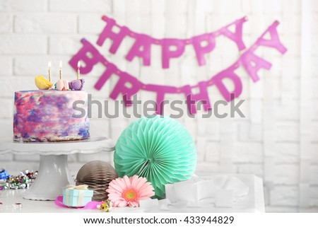 Tasty color cake with macaroons on table - stock photo