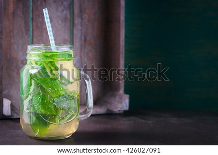 Tasty colorful drink with cold green tea, mint and cucumber in a glass jar on a vintage background, closeup, horizontal, with place for text - stock photo