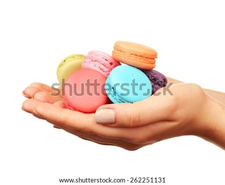Tasty colorful macaroons in female hands isolated on white - stock photo