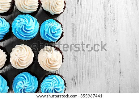 Tasty colourful cupcakes in a row on white wooden  background - stock photo