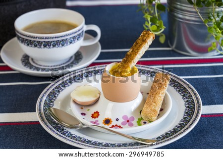 Tasty cooked breakfast of a boiled egg served in an egg cup, cup of freshly brewed coffee and pastries on a blue country-style tablecloth - stock photo