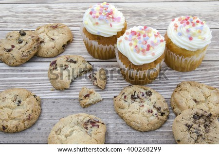 Tasty cookies and muffins cakes with vanilla cream decorated with sugar candies on a wooden background - stock photo