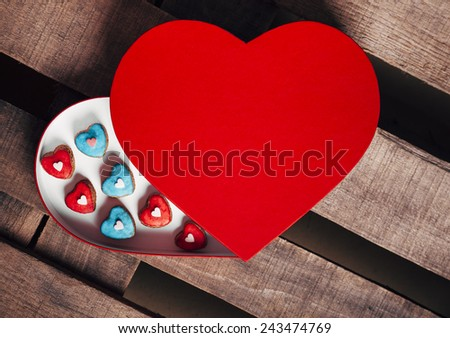 Tasty cookies in open valentines heart shaped box on a wooden table