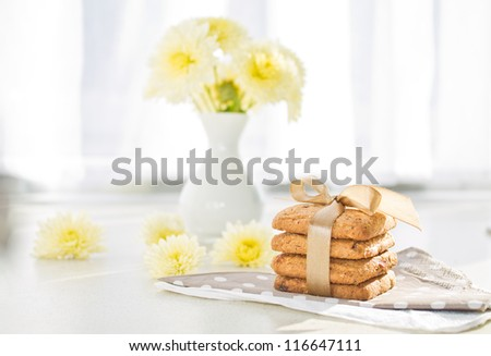 Tasty cookies on the napkin and flowers in background and on table in the morning - stock photo