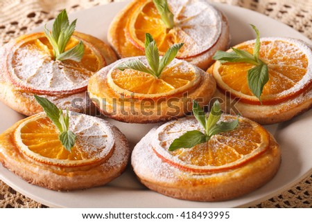 Tasty cookies with oranges, decorated with mint and powdered sugar close-up on a plate. horizontal