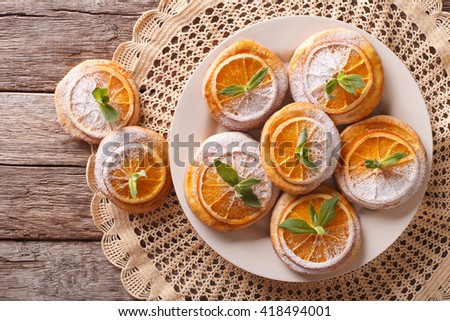 Tasty cookies with oranges, decorated with mint and powdered sugar close-up on a plate. Horizontal view from above