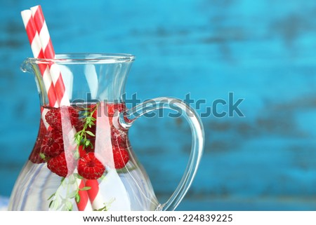 Tasty cool beverage with raspberries and thyme, on light background - stock photo