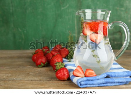 Tasty cool beverage with strawberries and thyme, on wooden background - stock photo