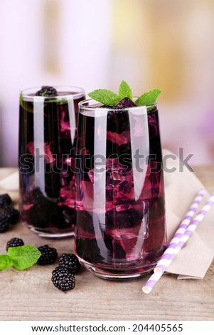 Tasty cool blackberry lemonade with ice on wooden table, on light background - stock photo