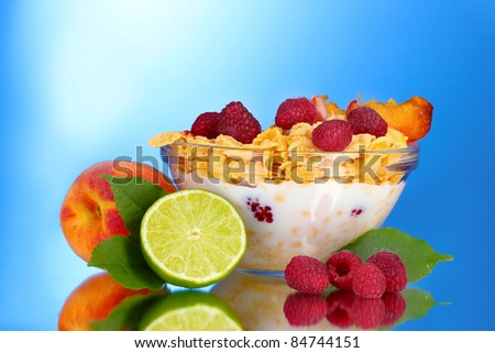 tasty cornflakes, fruit and milk in glass bowl on blue background