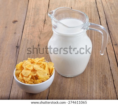 tasty cornflakes in white  bowl and glass of milk on wooden table