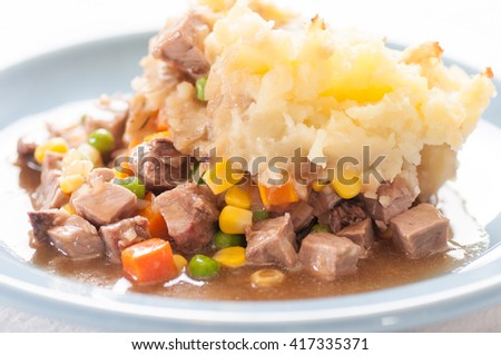 tasty cottage or shepherd's pie with fresh lmab and vegetables smothered in mashed potatoes - stock photo