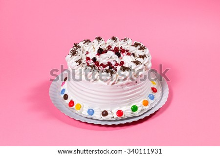Tasty creamy birthday cake colorful candy adorned on pink background - stock photo