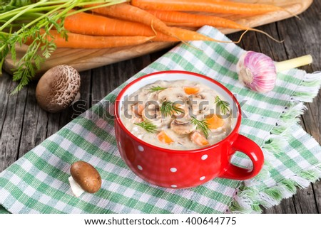 Tasty creamy cheese mushroom soup with spring carrots and veggies, decorated with dill, in a red cup on an old rustic table, top view - stock photo