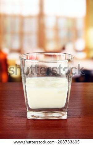 Tasty creamy liquor, on bright background - stock photo