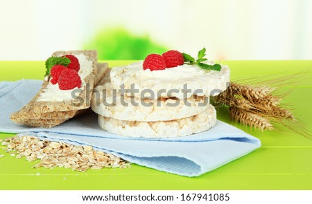 Tasty crispbread with berries, on green table