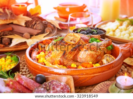 Tasty crispy chicken with baked vegetables on the centerpiece of table, family dinner in Thanksgiving day, traditional American holiday  - stock photo
