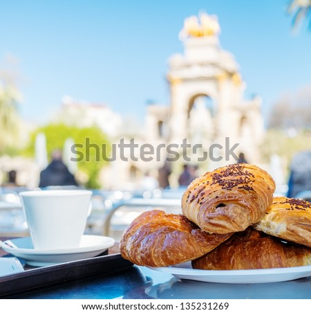 Tasty croissants with cup of coffee against famous fountain view in Barcelona - stock photo