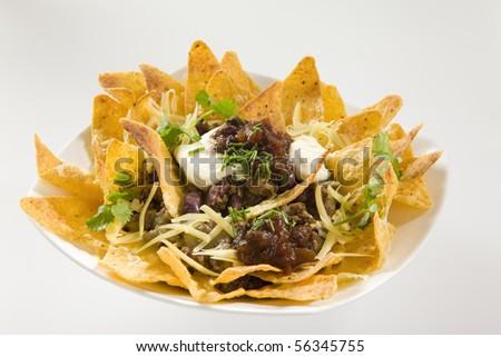 Tasty Crunchy Nachos served with sour cream - stock photo