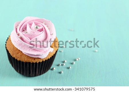 Tasty cupcake on color wooden background - stock photo